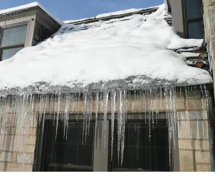 A building with snow on the roof and significant icicles