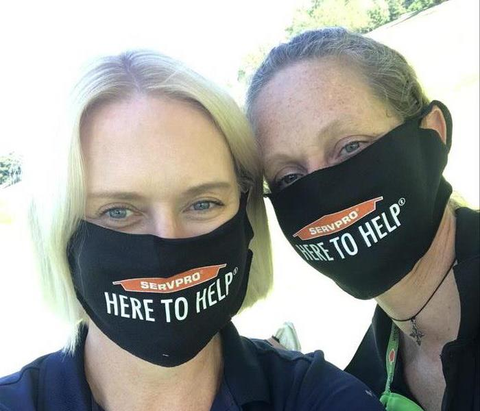 2 women in masks posing for pic at a golf outing